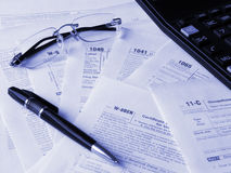 Taxes forms. Photo of the United States tax forms, pen, glasses and calculator. Toned blue. Shallow dof Stock Photo