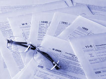 Taxes forms. Photo of the United States taxes forms and glasses. Toned blue. Shallow dof Stock Image