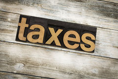 Taxes Letterpress Word on Wooden Background Royalty Free Stock Images