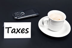 Taxes message on desk with coffee Royalty Free Stock Photos