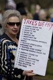 Taxes We Pay. Boston, Massachusetts USA - April 2013 - Woman holding list of Taxes We Pay at the Boston Tea Party rally on the Common Royalty Free Stock Images