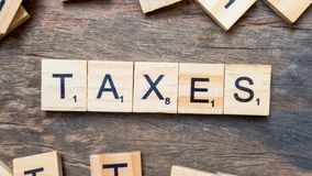 Taxes print text on wood square block. Concept of show keyword royalty free stock image