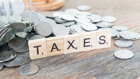 Taxes print text on wood square block on money coin. Concept of saving royalty free stock image