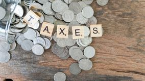 Taxes print text on wood square block on money coin. Concept of saving stock photography