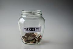 Taxes. Saved money for taxes in a glass jar Stock Photos