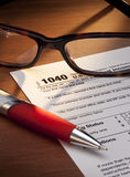 Taxes Tax 1040 Return Form. A macro still-life of a US 1040 Tax form returns with pen and glasses Stock Photos