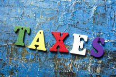 Taxes text on colorful wooden letters. Wood abc at blue grunge background Royalty Free Stock Photos