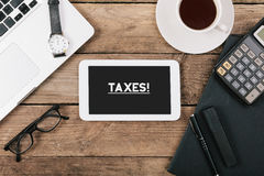 Taxes text on tablet computer on office desk Stock Image