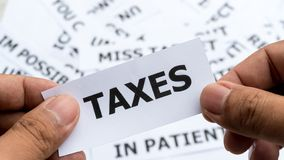 Taxes text or word meaning on paper in hand holding. Concept of show keyword stock photography