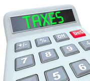 Taxes - Word on Calculator for Tax Accounting. A plastic calculator displays the word Taxes symbolizing the need to file annual tax returns Stock Images