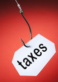 Taxes word on hook Stock Images