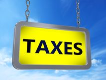 Taxes on billboard. Taxes on yellow light box billboard on blue sky background Stock Photos