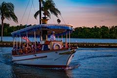 Taxi łódkowaty przyjeżdżać przy drzewkami palmowymi na kolorowym zmierzchu tle przy Walt Disney World terenem i wybrzeżem obrazy royalty free