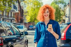 Taxi app. Woman using smart phone, standing on city street on su royalty free stock image