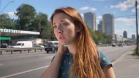 Taxi aspettante e condizione della giovane donna interessata dello zenzero sulla via urbana vicino alle emozioni sollecitata ed o archivi video