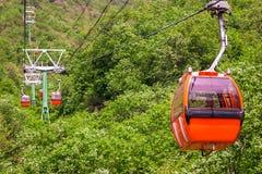 Taxi av orange färg av cablewayen på bakgrunden av berglandskapet arkivfoton