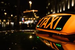 Taxi on the background of night city. The big taxi sign on the background of night city royalty free stock photography