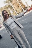 Taxi!. Beautiful young woman in suit hailing a ride and smiling while standing outdoors royalty free stock photo