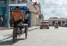 Taxi bike on the street - cuba. Life in holguin, cuba. A taxi biker is riding his bike on the cuban street Stock Images
