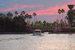 Taxi boat arriving at bridge on colorful palm trees and magenta sky background in Lake Buena V royalty free stock photo