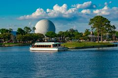 Taxi boat sailing and panoramic view of sphere Spaceship Earth attraction at  Epcot in Walt Disney World .