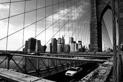 Taxi on Brooklyn Bridge. A typical NYC taxi is driving across Brooklyn Bridge from Manhattan to Brooklyn with the Downtown Manhattan skyline in the background Royalty Free Stock Images