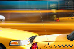 Taxi Cab Blur. This is a shot of some city taxis. A Mini-van type taxi can be seen in a blur passing in the parked taxis in the image Royalty Free Stock Photography