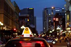 Taxi cab in downtown traffic at night Stock Photos