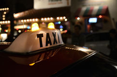 Taxi cab sign. Sign on a a taxi cab in the street at night time Royalty Free Stock Images