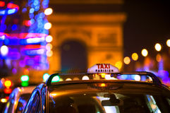 Taxi Cabs and Arc de Triomphe in Paris, France. Night scene at the Champs Elysees with iconic Parisian taxi cabs with view towards Arc de Triomphe Royalty Free Stock Photo