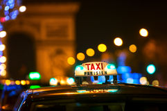 Taxi Cabs and Arc de Triomphe in Paris, France. Night scene at the Champs Elysees with iconic Parisian taxi cabs with view towards Arc de Triomphe Stock Photo