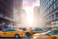 Taxi cabs in motion past crowds of people on Broadway in New York City. Taxi cabs in motion past crowds of people on Broadway with a colorful sunset in Manhattan stock image