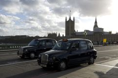 Black taxi cabs London. Taxi cabs were running across Westminster Bridge of London stock images