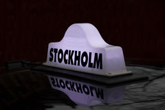 Taxi cap on a car roof Stock Images
