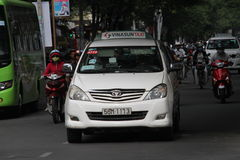 Taxi car in the city of Vietnam. White taxi car driving on a crowded road in the city of Vietnam Royalty Free Stock Photo