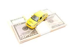 Taxi car and dollars. Yellow taxi car and banknotes on white closeup Stock Photos