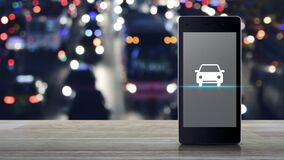 Taxi car flat icon on modern smart mobile phone screen on wooden table over blur colorful night light traffic jam street in city w