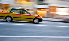 A taxi car in motion blur. A taxi car speeding down the street with a motion blur Stock Images