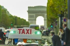 Taxi car sign and business people. Arc de Triomphe in background stock image