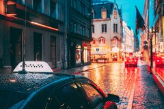 Taxi Car Wait Clients In Old European Streets In Rainy Evening. Night Street Illuminations. Taxi Car Wait Clients Near Cafe In Old European Streets In Rainy royalty free stock images