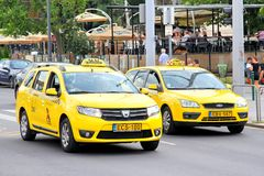 Taxi cars. BUDAPEST, HUNGARY - JULY 23, 2014: Yellow taxi cars Dacia Logan and Ford Focus at the city street Royalty Free Stock Photography