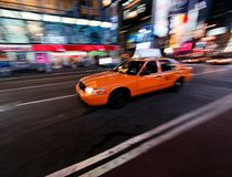 Taxi on city street. An orange cab speeding along on a city street at night in New York City.  Motion blur Stock Photography