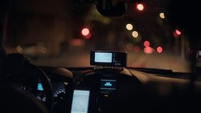 Taxi commuting at night. Closeup slowmotion shot of taximeter screen technology counting kilometers and fare due to be paid, installed in taxi driving through stock footage