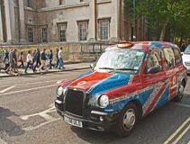 Taxi covered by Union Jack Flag. London taxi covered by Union Jack Flag during Queen Elizabeth's Silver Jubilee celebrations royalty free stock photo