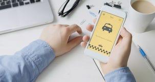 Taxi d'ordinazione facendo uso dell'applicazione dello smartphone stock footage