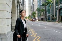 Taxi de attente asiatique de femme d'affaires Photos stock