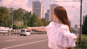 Taxi de granizada y situación de la mujer joven seria hermosa del jengibre en la calle cerca del camino, hembra encantadora en la almacen de video