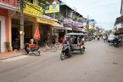 Taxi de touristes de Tuk-tuk sur la rue centrale du Siem Reap image stock