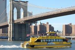 Taxi del agua de Nueva York en el puente de Brooklyn Imagenes de archivo