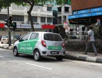 Taxi di GrabCar con gli annunci promozionali dipinti intorno al suo lato fotografie stock